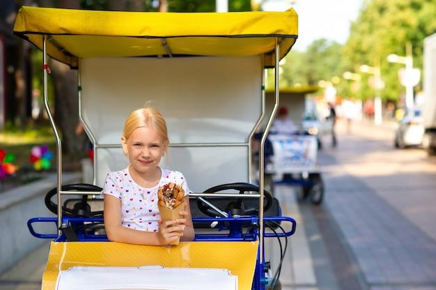 어린 소녀는 뿌리와 과자가있는 와플에 맛있고 아름다운 아이스크림을 손에 쥐고 있습니다.
