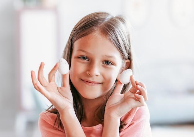 어린 소녀는 메추라기 알을 손에 쥐고 있습니다. 부활절 아침. 건강한 식생활
