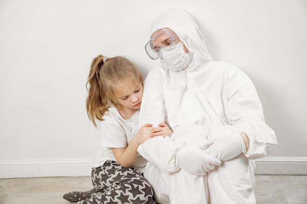 어린 소녀는 흰색 보호복, 마스크, 안경, 장갑을 끼고 의사를 껴안습니다. 레드존. 아기 환자입니다. 감사. 전염병 동안 약. 엄마는 의사다