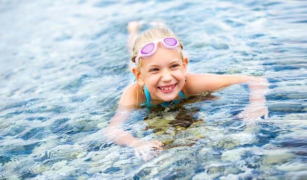 수영복을 입은 어린 소녀는 바다에 누워 웃고 있습니다. 어린 소녀는 물에 누워 웃고