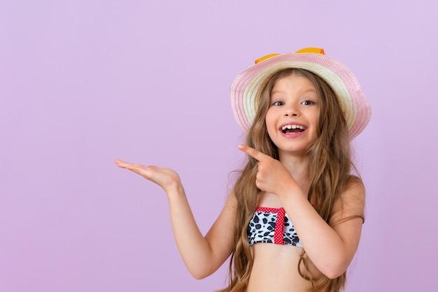 수영복을 입은 어린 소녀가 광고를 손가락으로 가리킵니다.