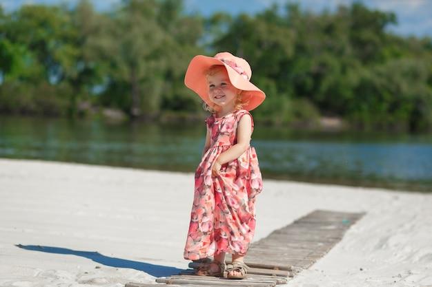 Маленькая девочка в красивой сарафне играет на песке на пляже.