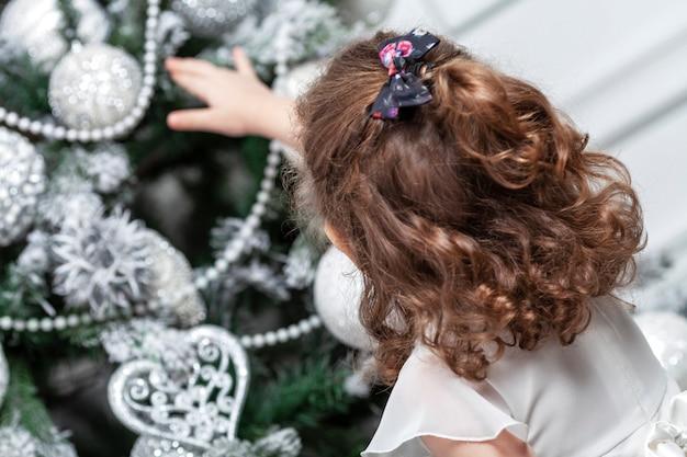 Маленькая девочка в красивом белом платье стоит возле игрушечного дерева, украшенного игрушками. новый год и рождество. вид сзади.