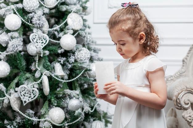 Маленькая девочка в красивом белом платье стоит возле игрушечного дерева, украшенного игрушками. новый год и рождество.