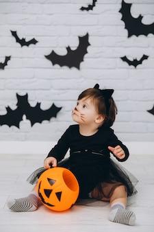 Маленькая девочка в костюме черного кота с тыквенной корзиной