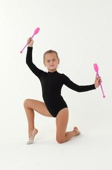 Маленькая девочка в черном трико гимнастки выполняет упражнение