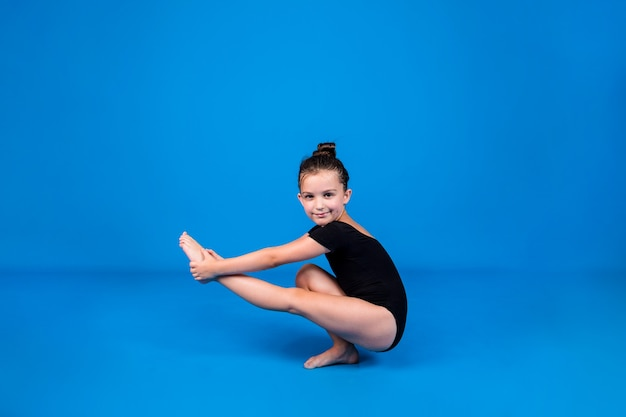 黒の水着の少女は、テキストの場所と青い背景でバランス運動を実行します