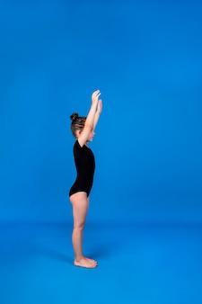 검은색 수영복을 입은 어린 소녀가 텍스트를 위한 장소가 있는 파란색 배경에서 워밍업을 수행합니다