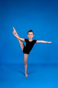 검은 수영복을 입은 어린 소녀가 텍스트를 위한 장소가 있는 파란색 배경에서 스트레칭 운동을 합니다