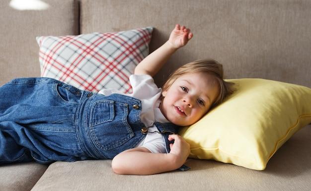 Маленькая девочка в синем джинсовом комбинезоне лежит дома на диване среди разноцветных подушек и весело улыбается.