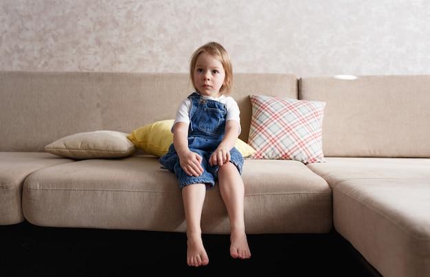 Маленькая девочка в синем джинсовом комбинезоне сидит на диване среди разноцветных подушек и смотрит в сторону.