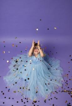 Маленькая девочка в голубом платье принцессы сидит на полу и ловит летящие конфетти на фиолетовом.