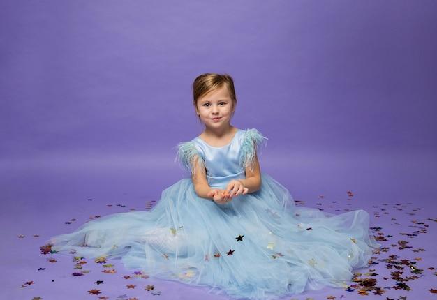 파란색 푹신한 드레스를 입은 어린 소녀가 보라색에 색종이 조각으로 바닥에 앉아 있습니다.