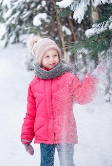 明るいジャケットを着た少女が冬の雪の森で遊んでいます。
