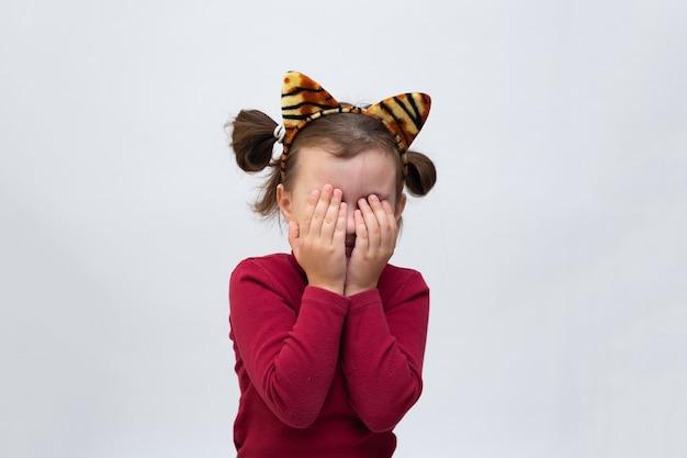 バーガンディのタートルネックに身を包み、虎の耳の縁を持った少女は、テキストの場所がある白い背景に手のひらで目を閉じました。