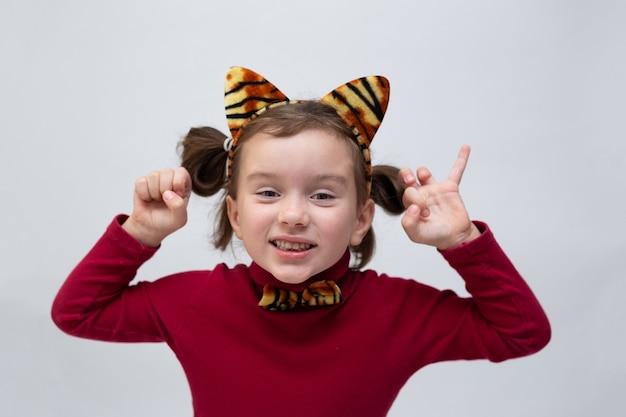 버건디 터틀넥을 입고 흰색 배경에 호랑이 귀가 달린 테두리가 있는 어린 소녀와 텍스트를 위한 장소