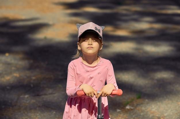 Маленькая девочка в кепке на скутере смотрит на солнце с закрытыми глазами