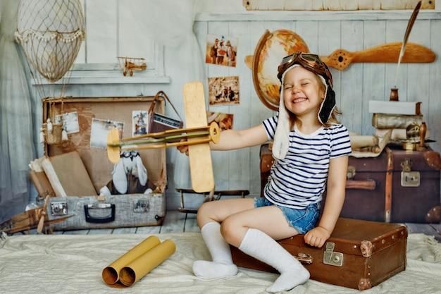帽子をかぶった少女がレトロなスーツケースに座って、手に木製の飛行機を持っています