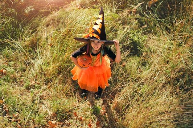 ハロウィーンの前夜、カーニバルの魔女の衣装と大きな帽子をかぶった少女が背の高い乾いた草の中に立っています。日没の晴れた日。トリックオアトリート。子供の手にカボチャ
