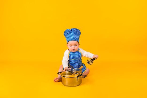 Маленькая девочка в костюме повара сидит с металлическим горшком на желтой стене с местом для текста