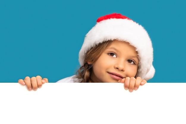 クリスマスの帽子をかぶった少女が背景の後ろから外を眺めています。