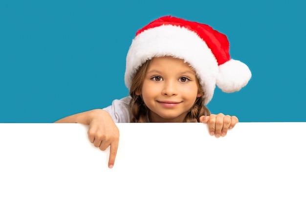 크리스마스 모자를 쓴 어린 소녀가 귀하의 광고를 가리 킵니다.