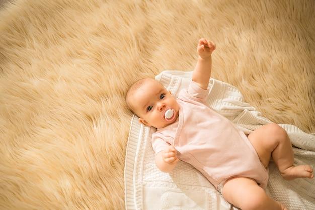 Маленькая девочка в цветном боди и с соской лежит на вязаном пледе и меховом пледе.