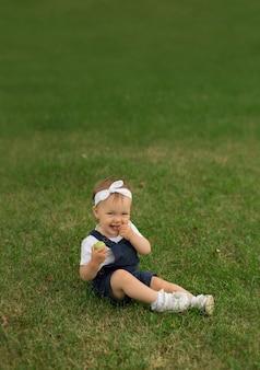 Маленькая девочка в джинсовом комбинезоне сидит в парке на траве и ест яблоко