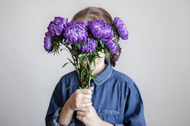 Маленькая девочка в джинсовой рубашке закрывает лицо букетом синих хризантем.