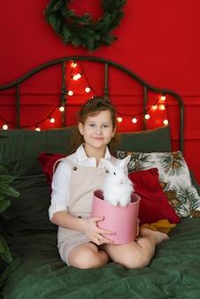 드레스를 입은 어린 소녀가 침대 옆 바닥에 앉아 상자에 앉아 있는 토끼를 바라보고 있습니다.