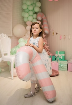 Маленькая девочка в пышном платье стоит и держит в новогодних украшениях шарик леденцом.