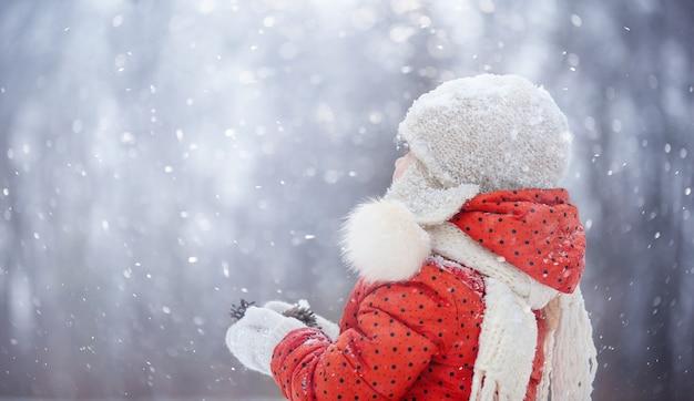 푹신한 모자를 쓴 어린 소녀가 눈 덮인 겨울 날 걷는다