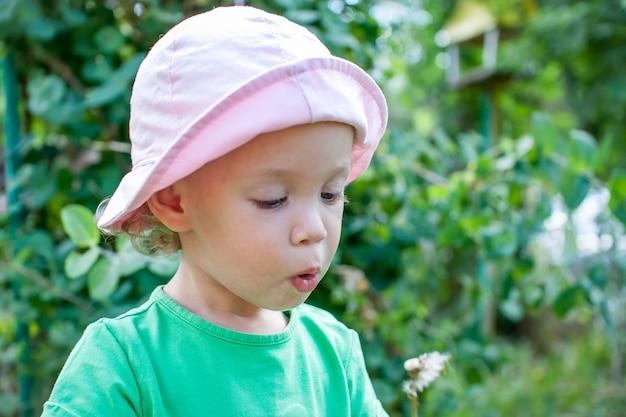 녹색 티셔츠와 분홍색 파나마를 입은 어린 소녀가 여름에 공원을 산책하고