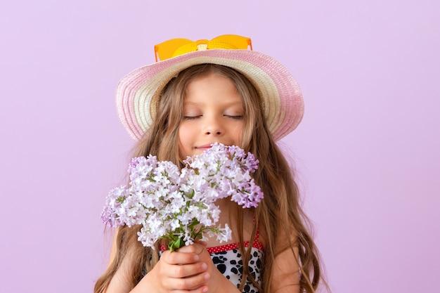 선글라스를 쓴 모자를 쓴 어린 소녀가 라일락 꽃다발을 들고 있습니다.
