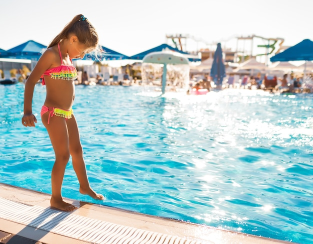 Маленькая девочка в ярко-розовом купальнике стоит у бассейна с прозрачной прозрачной водой и примеряет ногу.