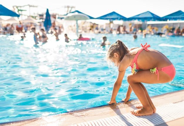 Маленькая девочка в ярко-розовом купальнике стоит у бассейна с прозрачной прозрачной водой и примеряет ее руками.