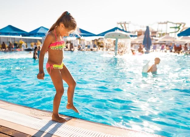 Маленькая девочка в ярко-розовом купальнике стоит у бассейна с чистой прозрачной водой