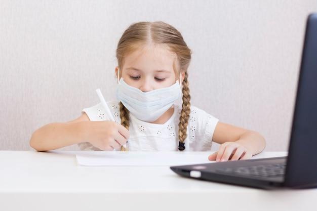 마스크를 쓴 어린 소녀가 테이블에 앉아 그림을 그리고 씁니다. 학생. 학교. 9월 1일. 가정 건강 격리