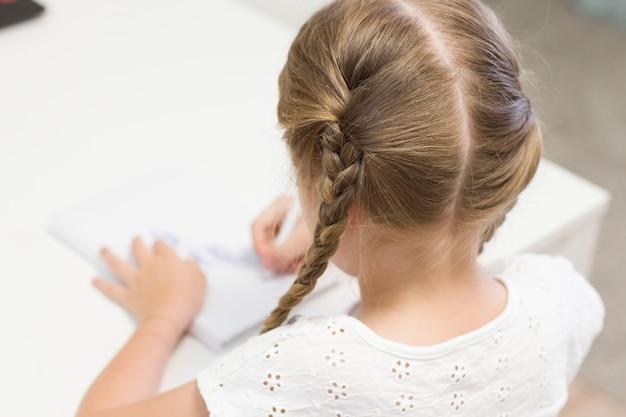 마스크를 쓴 어린 소녀가 테이블에 앉아 그림을 그리고 씁니다. 학생. 학교. 9월 1일. 프리미엄 사진