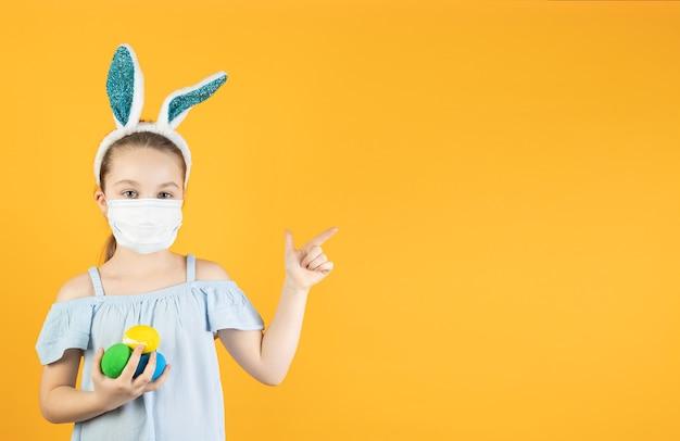 Маленькая девочка в медицинской маске от коронавируса на лице, на голове с заячьими ушками, держит в руках пасхальные яйца, указывает пальцем на пустое место для текста