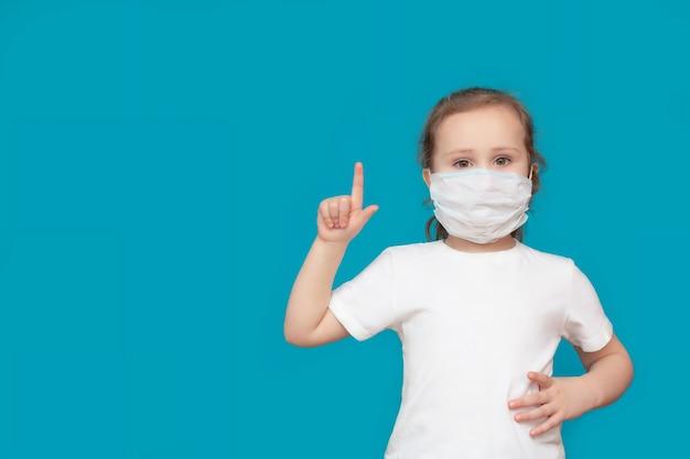 의료 마스크의 어린 소녀는 파란색 배경에주의를 경고하는 상징적 인 손 제스처를 보여줍니다.