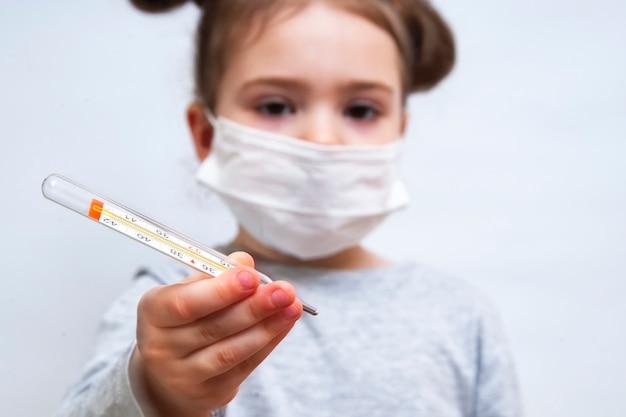 医療マスクの少女は、温度計を示しています。コロナウイルスの流行防止
