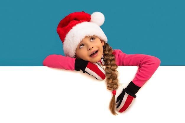 새해 모자를 쓴 어린 소녀가 광고에 몸을 기울였습니다.