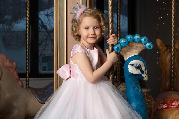 Маленькая девочка в розовом платье и короне на карусели с белым зайцем.