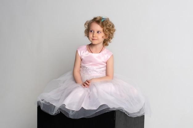 분홍색 드레스와 왕관에있는 어린 소녀는 흰색 바탕에 검은 색 입방체에 앉아있다.