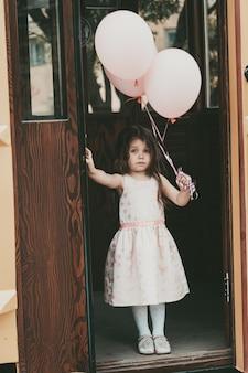 ピンクのドレスを着た小さな女の子がボールを持って路面電車から降ります。高品質の写真