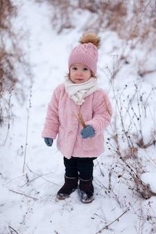 ピンクの毛皮のコートを着た小さな女の子が、雪に囲まれて外で遊んで楽しんでいます。冬の時間、健康な子供の活動の概念