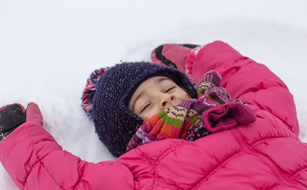 분홍색 재킷을 입은 어린 소녀가 갓 내린 눈 위에 천사를 만든다. 겨울 아이 재미 개념.