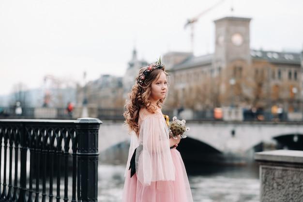 花束を手にピンクのプリンセスドレスを着た少女がチューリッヒの旧市街を歩きます。スイスの街の通りにピンクのドレスを着た少女の肖像画。