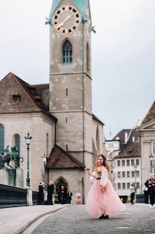 花束を手にピンクのプリンセスドレスを着た少女がチューリッヒの旧市街を歩きます。スイスの街の通りにピンクのドレスを着た少女の肖像画